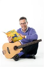 Eric Litwin sitting on floor with guitar